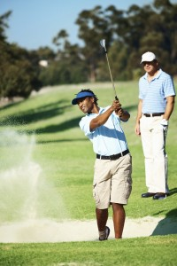 African American golfer swinging from a sand bunker, a friend in the background