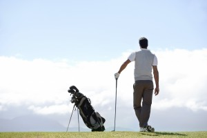 Mature golfer standing and admiring the view on the golf course alongside his clubs - rear view