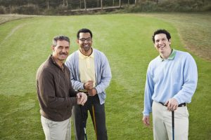 Multi-ethnic men playing golf.