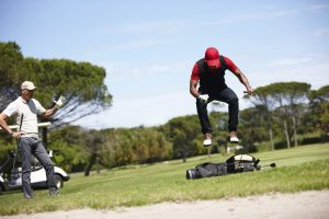 Shot of a frustrated golfer jumping on his golf bag